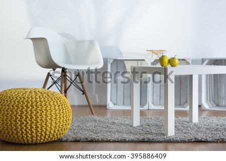 Yellow pouf, white armchair and coffee table in modern designed loft  - stock photo