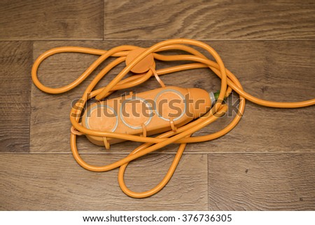 yellow power extension cord on the floor - stock photo