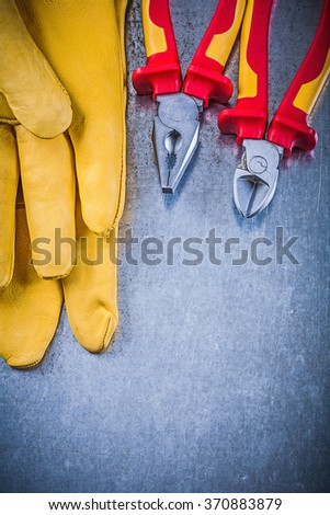 Yellow protective gloves pliers wire-cutter on metallic background electricity concept. - stock photo