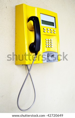 Yellow public telephone - stock photo