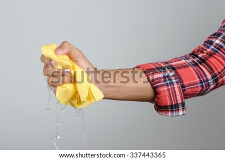yellow PVA chamois for car cleaning in man's hand - stock photo