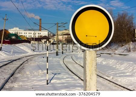 Yellow railroad sign on snow rails - stock photo