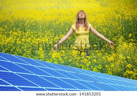 Yellow rapeseed field and solar panels. - stock photo