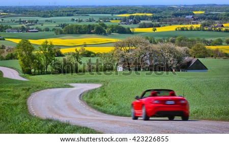 Yellow rapeseed fields and a red car in Sweden  - stock photo