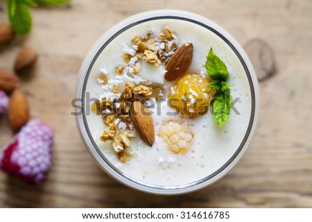 Yellow raspberries smoothie with coconut and almonds - stock photo