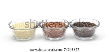 Yellow, red, and black quinoa in glass bowls isolated on a white background. - stock photo