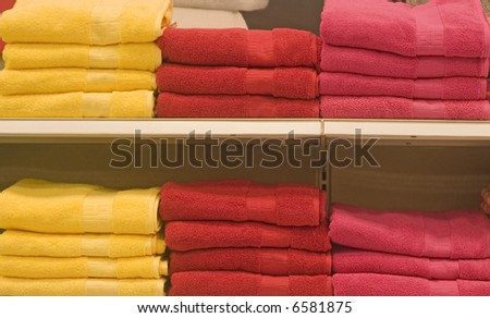 Yellow Red and Pink towels in a retail store
