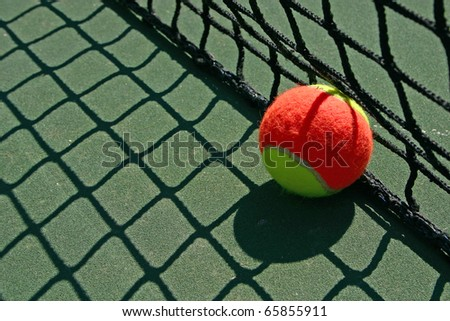 Yellow-red balls on a green tennis court - stock photo