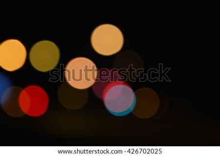 Yellow, red, blue, brown defocused blurry circular night city lights glowing soft in the darkness with bright colors. They soothe, brings a positive and located on the left in the middle of the photo. - stock photo