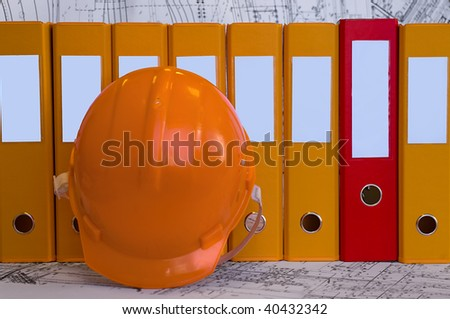 Yellow, red file folders, helmet are on the table. Business still-life. Clear place for your text. - stock photo