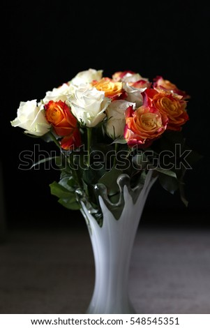 Yellow-red, orange and white roses in a vase on a dark background