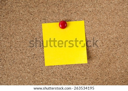 yellow reminder sticky note on cork board, empty space for text - stock photo