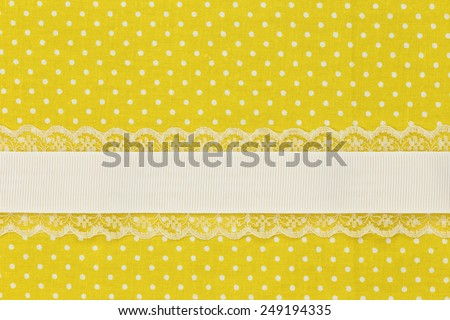 Yellow retro polka dot textile background with ribbon - stock photo