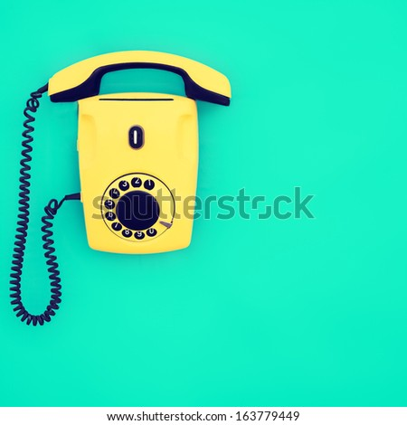 Yellow retro telephone on a blue background - stock photo