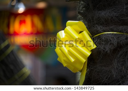 Yellow ribbon tied around a tree along the Riverwalk in San Antonio, TX - stock photo