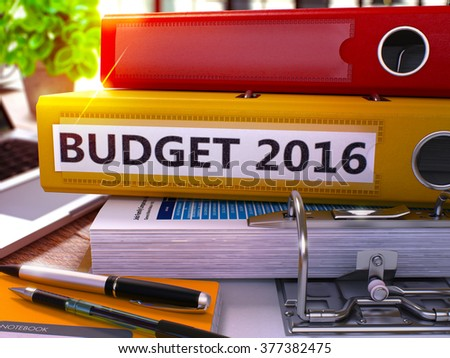 Yellow Ring Binder with Inscription Budget 2016 on Background of Working Table with Office Supplies and Laptop. Budget 2016 Business Concept on Blurred Background. 3D Render. - stock photo