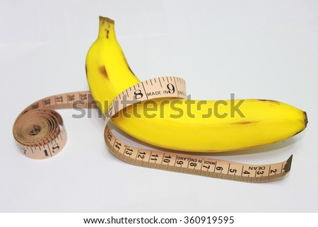 Yellow ripe banana with measuring tape. May indicate male's penis size or length. Related men's health. Or indicate banana can use for diet or keep fit purposes. - stock photo