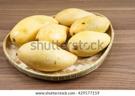 Yellow ripe fresh mango isolated on wooden background. DOF and copy space.  - stock photo
