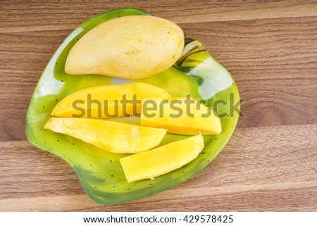 Yellow ripe fresh mango isolated on wooden background. DOF and copy space.