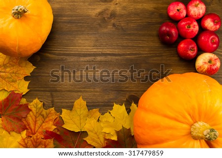 Yellow ripe pumpkin, maple leaves, red apples on wooden background. Thanksgiving, autumn. - stock photo