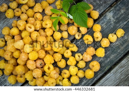 Yellow ripe raspberries, pineapple variety, on a wooden table