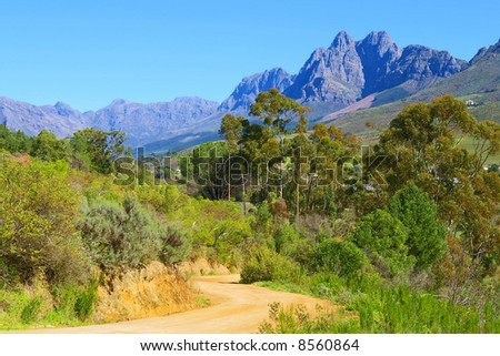 Yellow road in mountains. Shot in August, near Stellenbosch, South Africa. - stock photo