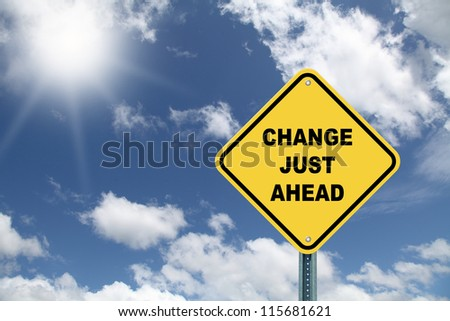Yellow road sign change just ahead on blue cloudy sky background - stock photo
