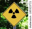 Yellow road sign outdoor with nuclear pictogram - stock photo