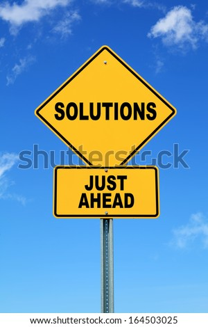 Yellow road sign solutions just ahead - stock photo