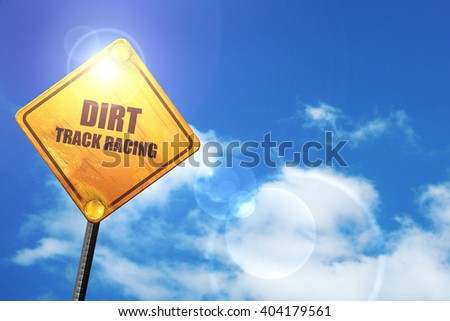 Yellow road sign with a blue sky and white clouds: dirt track ra