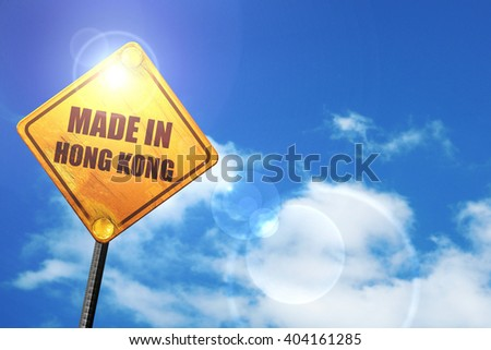 Yellow road sign with a blue sky and white clouds: Made in hong kong