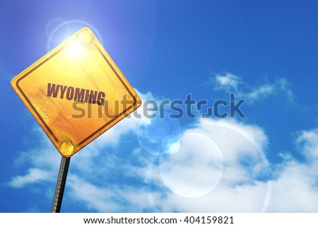 Yellow road sign with a blue sky and white clouds:  wyoming