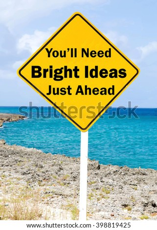 Yellow road sign with a You'll Need Bright Ideas Just Ahead concept against a coastal setting with a partly cloudy sky background. - stock photo