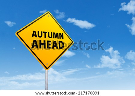 Yellow road sign with an autumn ahead text under blue sky - stock photo