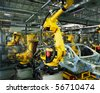yellow robots welding cars in a production line - stock
