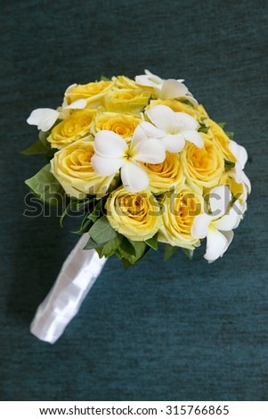 Yellow rose wedding bouquet on green background