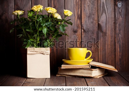yellow roses in pot, tea cup and old books on wooden table - stock photo