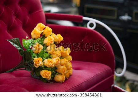 yellow roses on a red seat of a wedding carriage