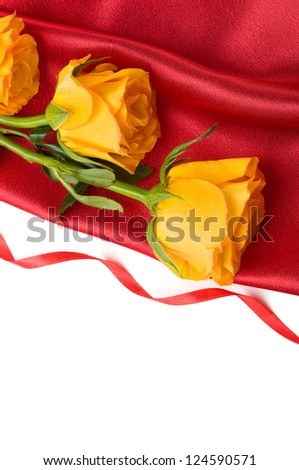 Yellow roses on red satin on the white with copy space - stock photo