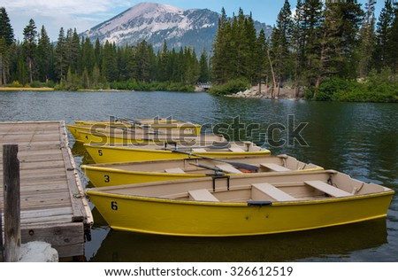 Yellow Rowboats At the Dock On a Lake with Pine Trees - stock photo