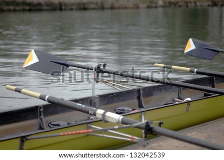 Yellow rowing boat of a Oxford University college with oars out on the river Isis in Oxford - stock photo