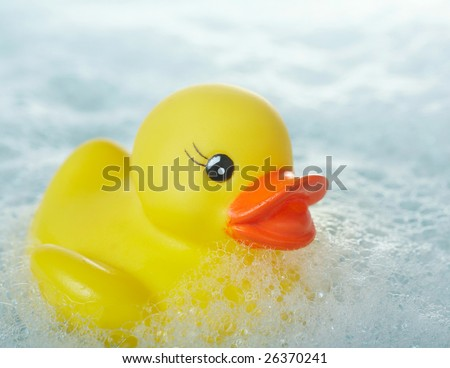 Yellow rubber ducky floating in soapy water - stock photo