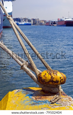 Yellow rusty metal bollard and ship rope - stock photo