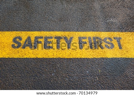 yellow safety first sign on the gray cement floor - stock photo