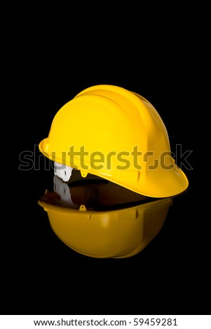 yellow safety hard hat, right hand side angle shoot, studio shoot isolated on black with reflection - stock photo