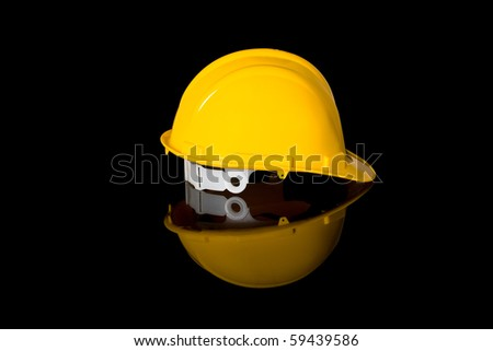 yellow safety hard hat, right hand side shoot, studio shoot isolated on black with reflection - stock photo