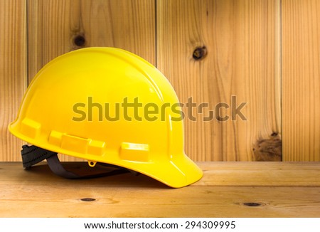 Yellow Safety Helmet on Wooden Floor with Wood Wall Background , color pop tone