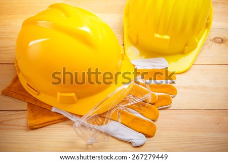 Yellow safety helmet or hard hat on wood board - stock photo