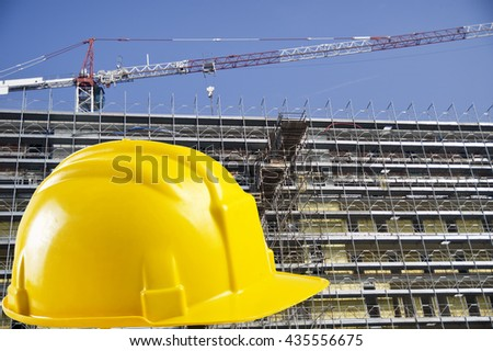 Yellow safety helmet with construction site background - stock photo