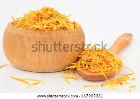 Yellow saffron, tasty and costly spice in wooden bowl and wooden teaspoon isolated on white background - stock photo
